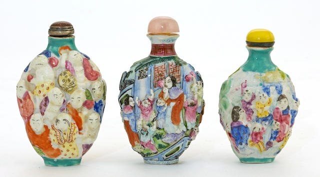 Three famille rose enameled porcelain porcelain snuff bottles with figures molded in raised relief  Qianlong marks