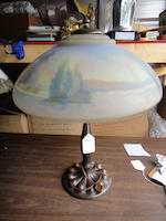 A Pairpoint and Duffner and Kimberly reverse-painted glass and patinated metal scenic table lamp<BR />first quarter 20th century
