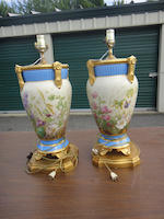 A pair of floral painted porcelain urns later mounted as table lamps 20th century, probably French