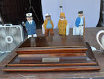 A mahogany cigarette box and a set of four carved and painted sailors<BR /> Modern, 20th century 4 x 15 x 10 in. (10.1 x 38.1 x 25.4 cm.) the box; 7 in. (17.7 cm.) height of each figure. 5