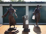 A group of three patinated bronze figures: St. Francis of Assisi and two peasant women<BR />20th century