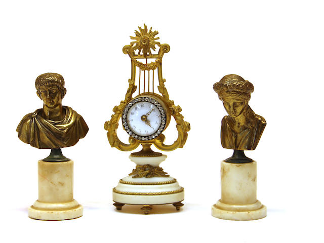 A French gilt bronze, paste jewel and marble lyre form desk clock and two gilt bronze classical busts late 19th/early 20th century