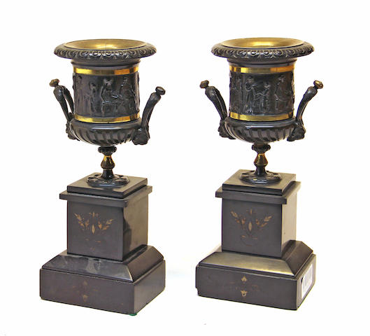 A pair of Greek revival patinated, parcel gilt bronze and slate two handle mantel urns fourth quarter 19th century