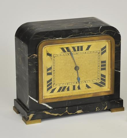 An Art Deco style Portor marble and gilt metal mantel clock