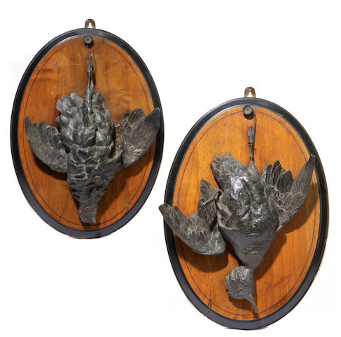 A pair of patinated metal wall plaques depicting dead game on oval back plates