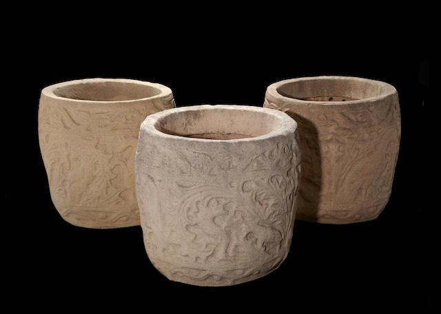 A set of three Michael Taylor Romanesque style cast stone jardinières