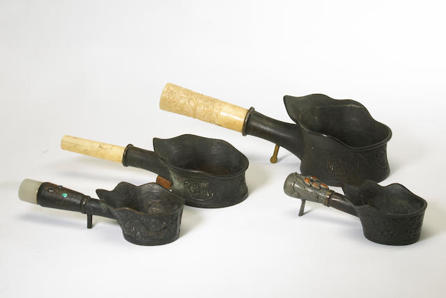 A group of four bronze brazier irons