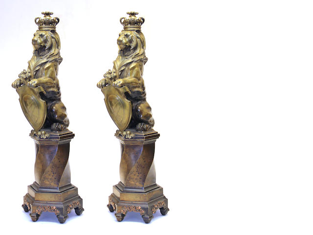 A pair of Baroque style cast brass heraldic lions on pedestals first quarter 20th century
