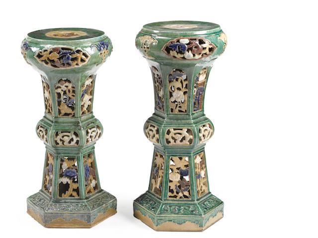 A pair of green and polychrome enameled pottery plant stands