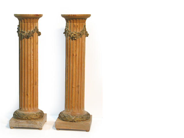 A pair of Continental Neoclassical style pine and parcel giltwood pedestals