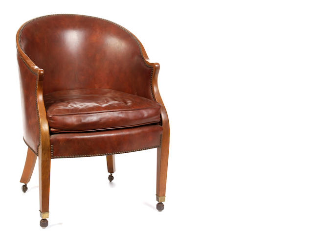 An Empire style brass studded and leather upholstered walnut bergère