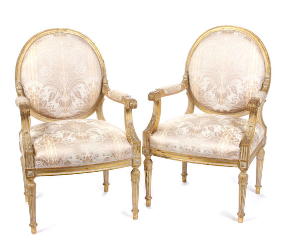 A pair of Louis XVI style parcel gilt paint decorated fauteuils