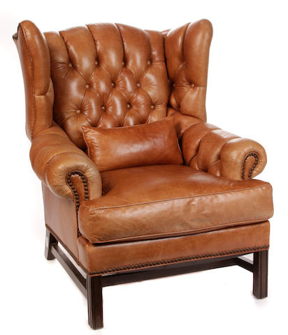 A George III style brass studded tufted leather wing armchair