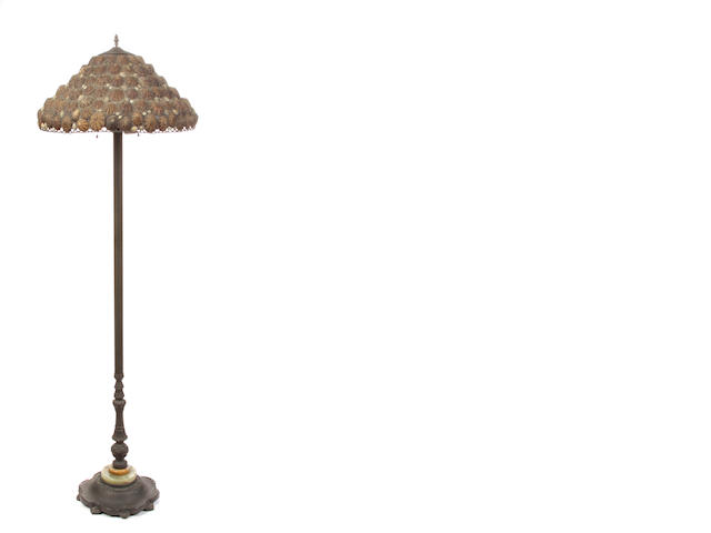 A patinated metal floor lamp with shell shade