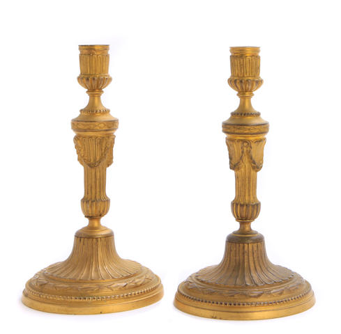 A pair of Louis XVI style gilt bronze candlesticks