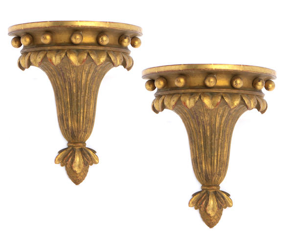 A pair of Neoclassical style gilt heightened earthenware wall brackets