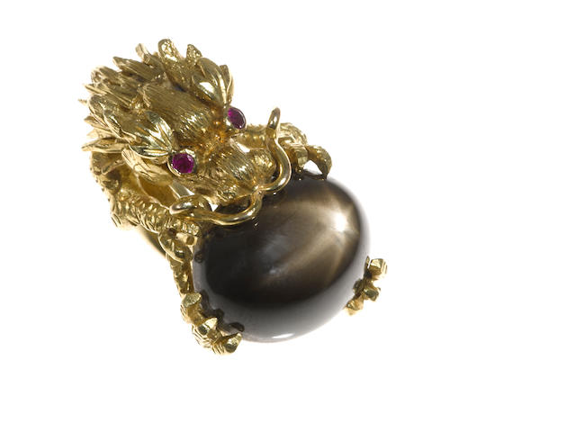 A black star sapphire, ruby and eighteen karat gold dragon motif ring
