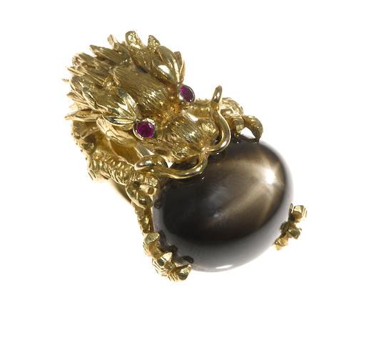 A black star sapphire, ruby and eighteen karat gold dragon motif ring