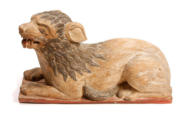 A polychrome carved wood figure of a recumbent lion