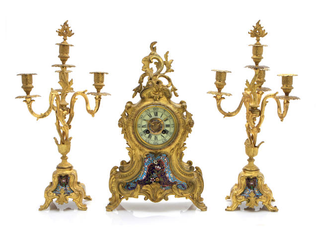 A Louis XV style enameled and gilt bronze three piece clock garniture