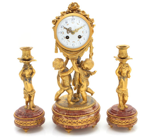 A Louis XVI style gilt metal and red marble clock garniture