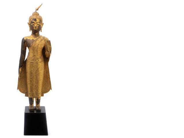 A gilt decorated metal figure on pedestal