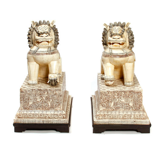 A pair of pierced bone tile seated Fu lions