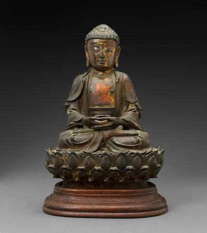 A Chinese cast bronze seated figure of Buddha on a separetly cast lotus form base and wood stand Ming dynasty