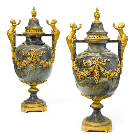 An imposing pair of gilt bronze and marble covered urns