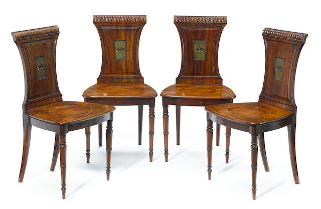 A set of four Regency mahogany hall chairs, the backs with armorial crests  <BR />possibly by Gillows