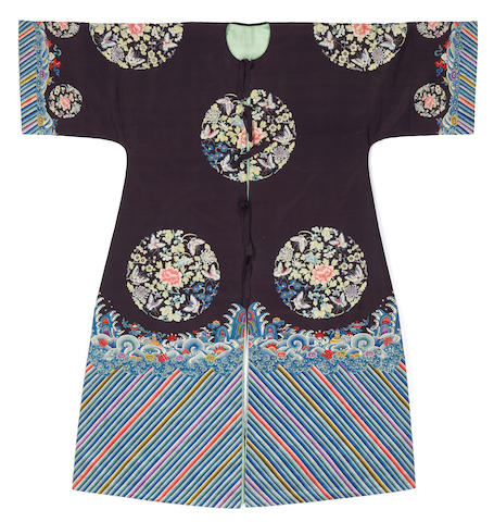 A Chinese blue ground lady's coat with embroidered floral and butterflies medallion decoration, Late Qing