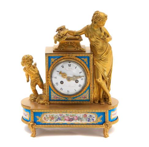 A Louis XVI style porcelain inset gilt bronze mantel clock