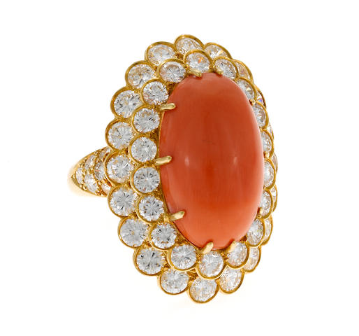 A coral, round brilliant cut diamond and gold ring