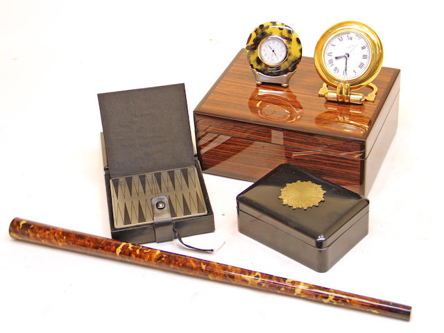 Two Cartier gilt-metal desk clocks, ebonized box with applied gilt bronze sunburst; tortoisehell veneered drumstick; miniature game box and a wood box