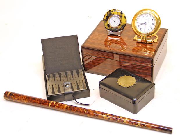 Two Cartier gilt-metal desk clocks, ebonized box with applied gilt bronze sunburst; tortoisehell veneered drumstick; miniature game box and a wood box