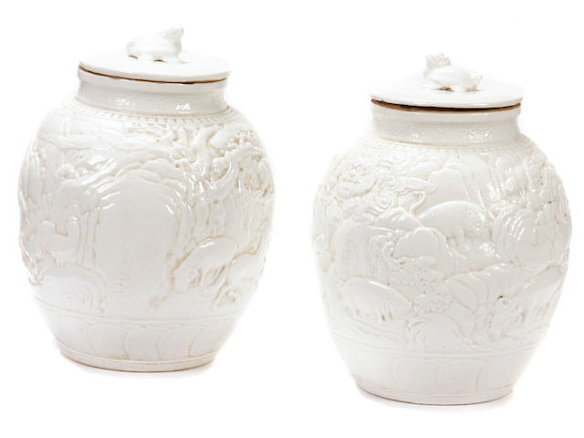 A pair of Chinese white glazed covered jars