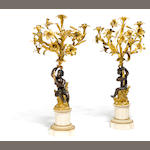 A pair of Louis XVI style gilt and patinated bronze and marble five light figural candelabra