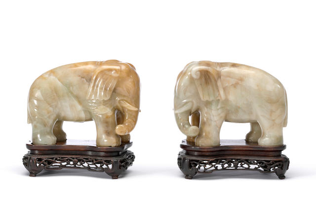 A pair of carved jade elephants early 20th century With matching wood stands.