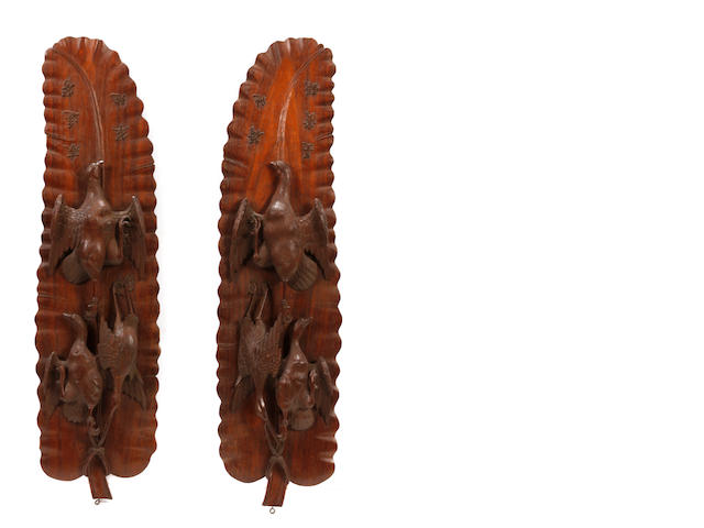 A pair of carved hardwood trophies in the Asian taste