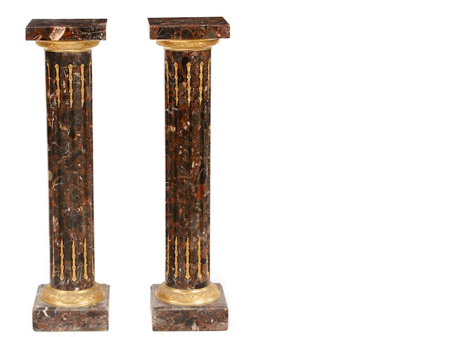 A pair of Louis XVI style gilt bronze mounted marble pedestals