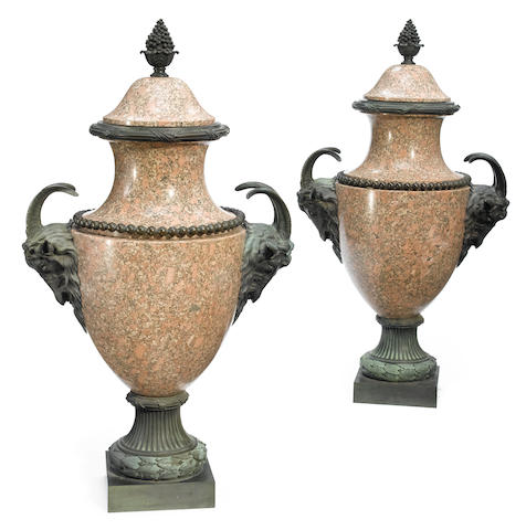 A pair of patinated bronze and granite covered urns