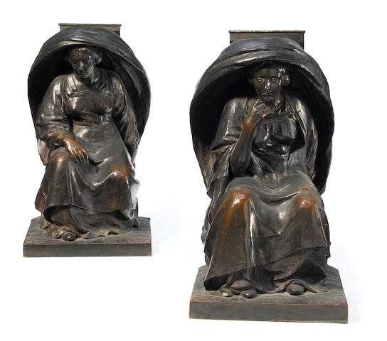 A pair of French patinated bronze plinths modeled as seated women