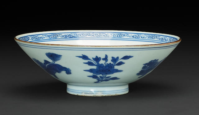 A blue and white porcelain bowl with fu lions and peonies, brown rim and peony center six character Jiajing mark, Transitional