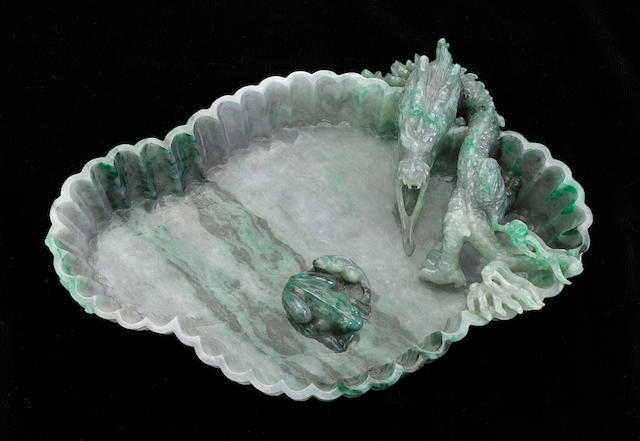 A mottled green jadeite footed tray with carved dragon design