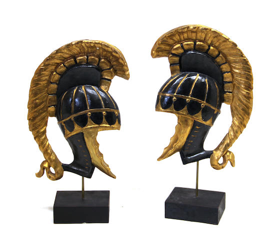 A pair of Italian giltwood and parcel ebonized helmet-form decorations on ebonized display stands