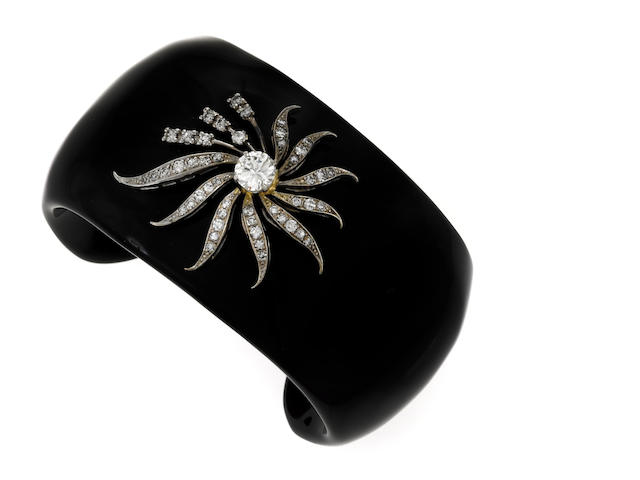 A black onyx cuff bracelet with white gold and diamond flower form applique