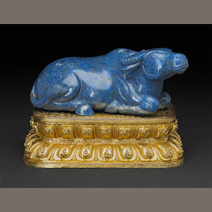 A carved lapis lazuli buffalo with gilt bronze stand