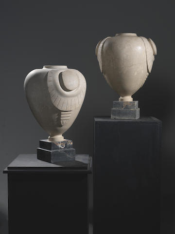A Pair of Carved Stone Botticelli Urns French, circa 1920  on polished marble bases  Height: 20 7/8 in. 53 cm.