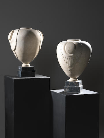 A Pair of Carved Stone Botticelli Stone Urns French, circa 1920  on polished marble bases  Height: 20 7/8 in. 53 cm.