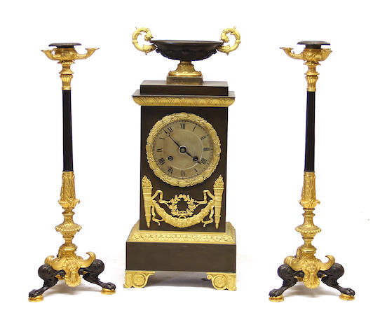 A Charles X gilt and patinated bronze mantel clock and pair of Pompeian style candlesticks second quarter 19th century